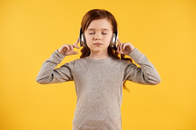 Concentrated little girl in headphones listens to classics.