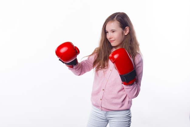 Concentrated little girl is wearing some red gloves for box.
