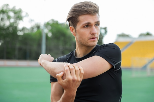 Concentrated male athlete make stretching exercises outdoors
