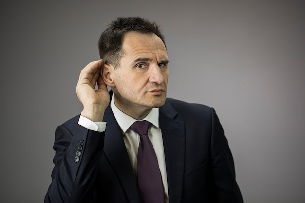 Concentrated male businessman with hand at ear trying to hear something