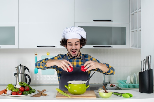 Concentrated male chef with fresh vegetables holding red peppers in the white kitchen