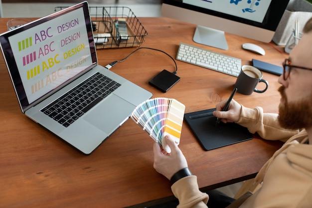 Концентрированный дизайнер-мужчина пишет текст на блокноте и выбирает цвет шрифта