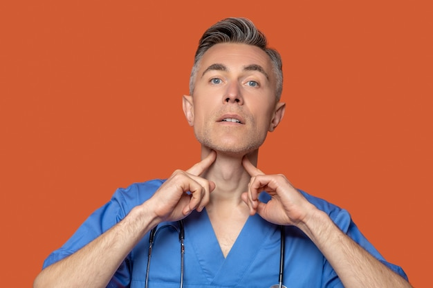Concentrated male doctor touching fingers with neck