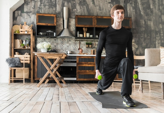 Concentrated male doing exercises with dumbbells