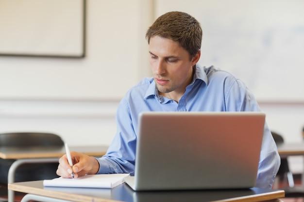 Концентрированный мужчина зрелого студента, используя свой блокнот для обучения