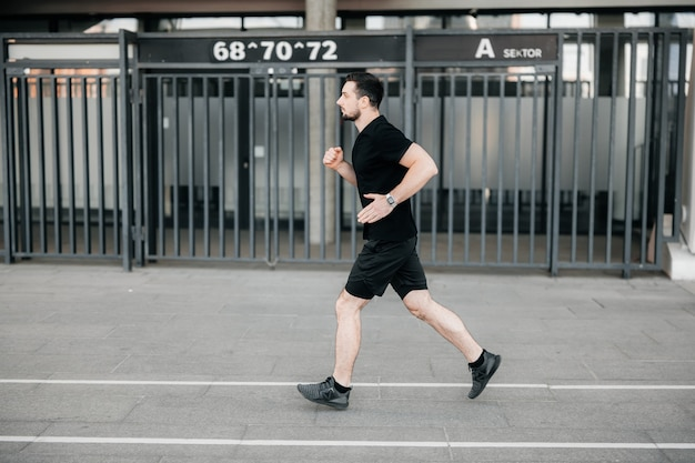 Concentrated male runner excercising at morning. urban city lifestyle concept. athletic man in black sport clothes and sneakers jogging outdoors. healthy lifestyle. man running. active living.