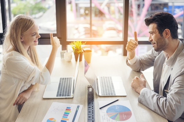 集中した男性と女性の労働者がノートパソコンを使用して交渉するオフィスの机に座ってアイデアについて話し合い、多様な同僚がブレーンストーミングでビジネスプロジェクトについて交渉します。協力コンセプト