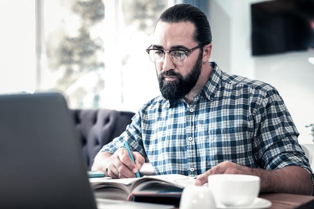 集中した男。雑誌の記事を扱うことに集中していると感じているひげを生やした暗い目の男