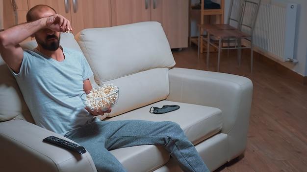 Сосредоточенный мужчина отдыхает на диване перед телевизором, смотрящим сериал