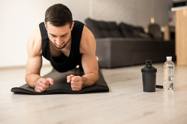 Concentrated man doing plank position while exercising on black yoga mat. water bottles lying near. smart modern interior on backgroung. man in black sportswear exercising at home.