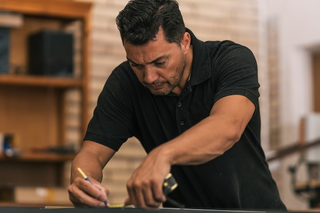 작업장에서 미터를 사용하여 표면에 그림을 그리는 집중된 남자