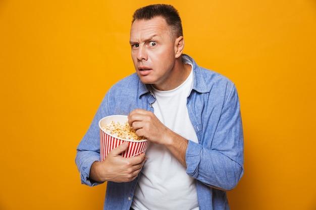 Сосредоточенный человек ест смотреть фильм смотреть поп-корн.