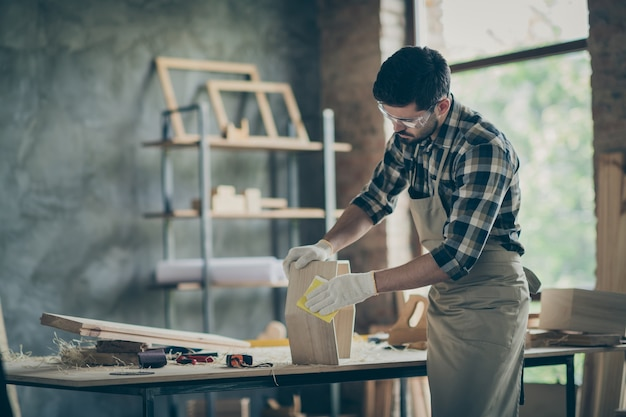 Сосредоточенный бригадир работает с деревянной полкой, отремонтированной, обновленной мебелью на столе в домашнем гараже