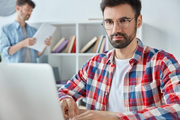 집중된 남자 프리랜서가 랩톱 컴퓨터에서 먼 거리에서 일하고 수염이 있고 안경을 쓰고 있습니다.