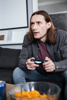 Concentrated man gamer sitting at home indoors