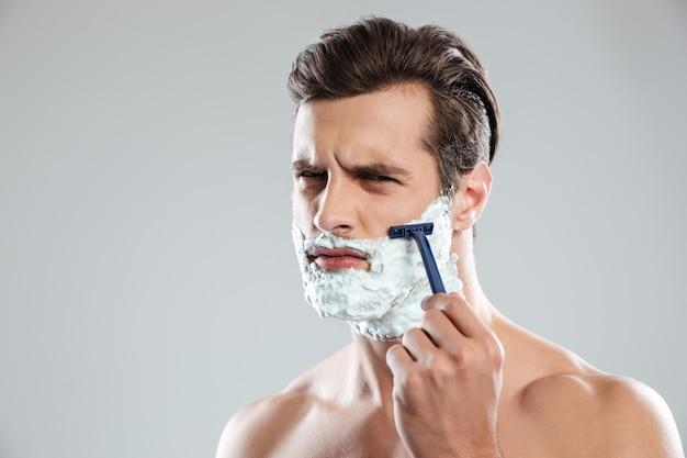 集中した男はひげをそる