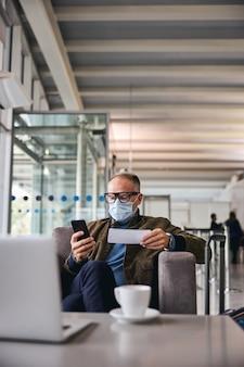 Сосредоточенный человек в маске смотрит на свой смартфон