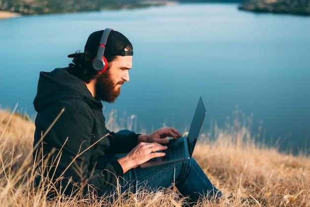 音楽を聴き、川の近くのフィールドでコンピューターに取り組んでいる集中した男