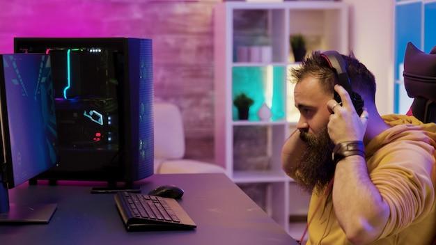 화려한 네온으로 방에서 pc로 비디오 게임을 하는 집중된 남자. 밤에 비디오 게임을 하는 남자.