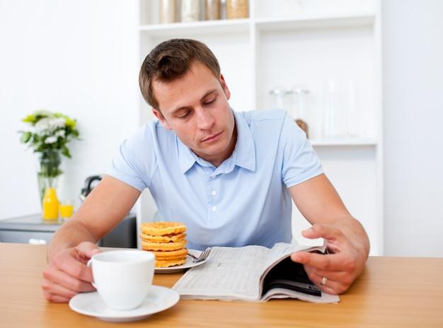 朝食を取っている間に新聞を読んでいる集中した男