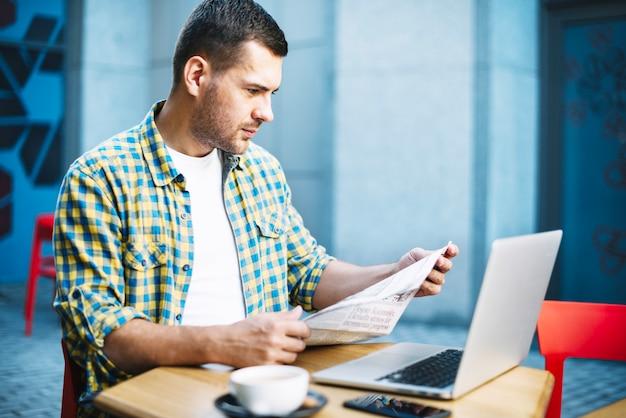 テーブルでニュースを読んで集中している男