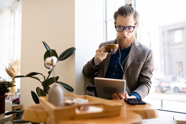 Сконцентрированный человек читая онлайн книгу в кафе