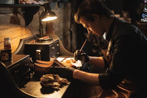 靴のワークショップで男の靴屋を集中。