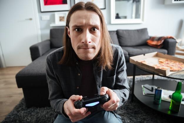 Сконцентрированный человек сидя дома в помещении играет в игры