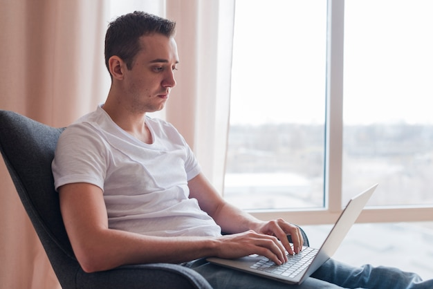 Concentrated man sitting on chaor and typing on laptop near window