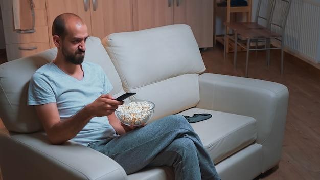 Сосредоточенный мужчина сидит перед телевизором с пультом дистанционного управления