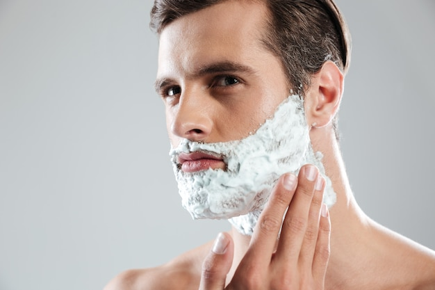 Сконцентрированный человек стоя изолированный с пеной для бритья на лице