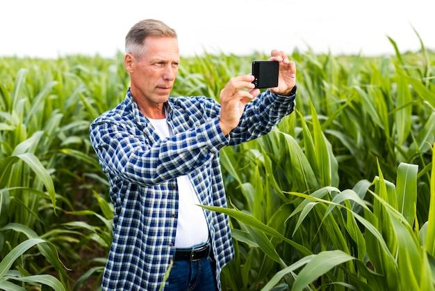 Uomo concentrato che prende un selfie