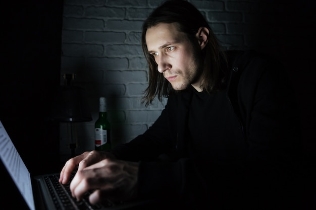 Concentrated man using laptop computer at home indoors