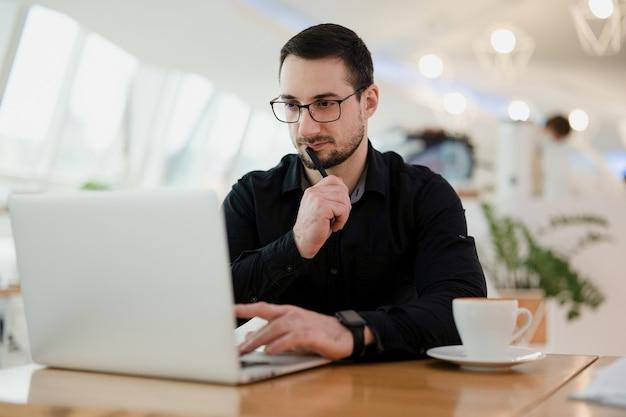 ノートパソコンを使用し、口の近くにペンを持ち、自分の仕事について考えている集中した男性。カフェで働きます。眼鏡と黒いシャツのプログラミングを身に着けているひげを持つ魅力的なインテリジェントな男。