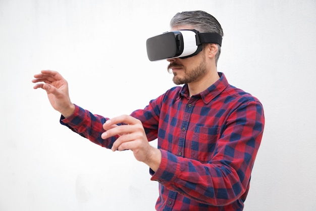 Concentrated man in vr headset touching air
