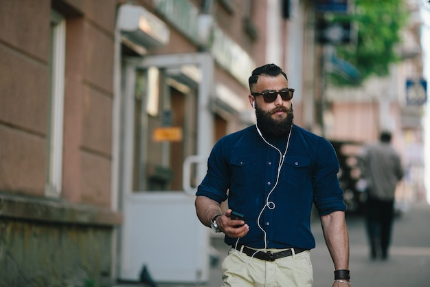 Concentrated man walking while listening to music