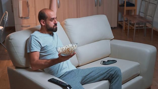 Сосредоточенный мужчина смотрит развлекательный фильм, делая выражение лица