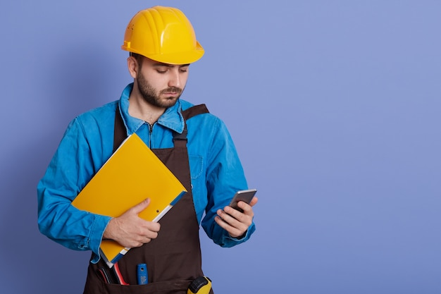 Concentrated man wearing protective helmet and apron holding yellow paper folder and mobile phone in hands, looking a device's screen