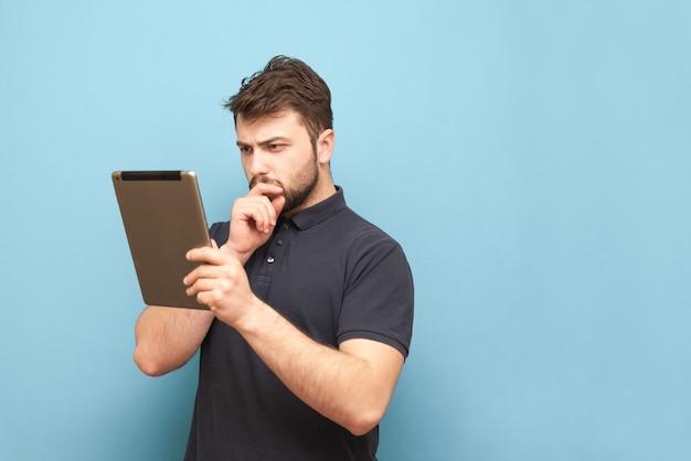 あごひげとtシャツを着た集中力のある男が青に立ち、暗いtシャツを着て画面を注意深く見ています。