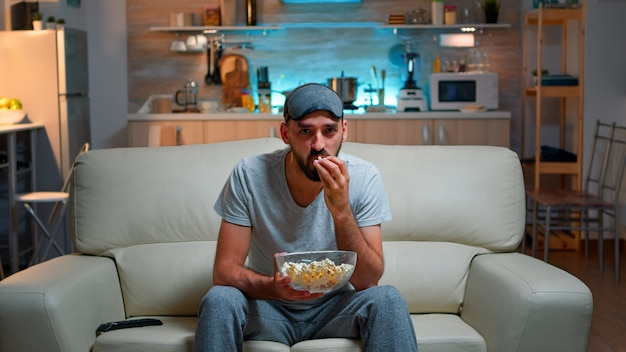 Concentrated man with sleep eye mask sitting in front of television