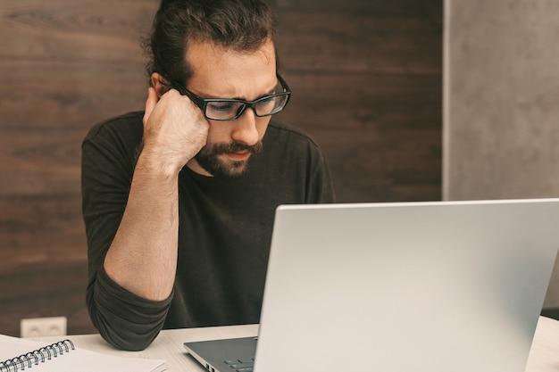 ノートパソコンを使用して在宅勤務の集中男性
