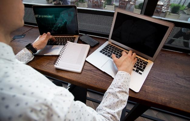 Сосредоточенный человек работает на своих ноутбуках