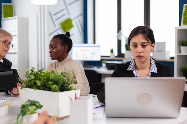 スタートアップビジネスオフィスの机に座ってラップトップに入力する集中マネージャー。バックグラウンドで作業している多様な同僚。新しい金融プロジェクトを計画している多民族の同僚。