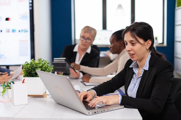 スタートアップオフィスの机に座ってラップトップに入力する集中マネージャー