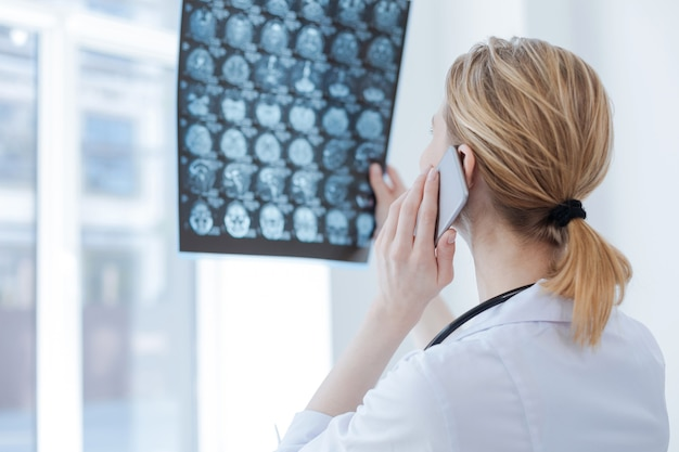 Concentrated masterful skilled radiologist working at the clinic while holding brain x ray and using smartphone for conversation