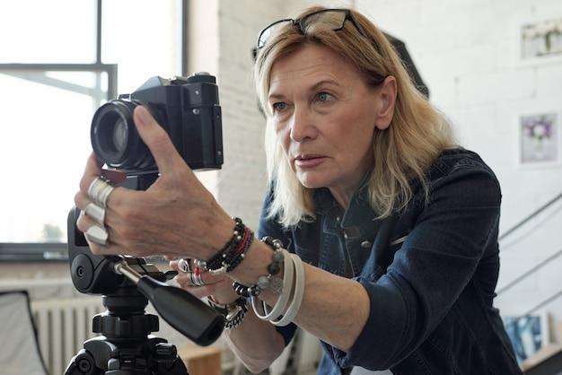 現代のスタジオで写真を撮っている間、ブロンドの髪の調整カメラレンズを持つ集中した成熟した女性