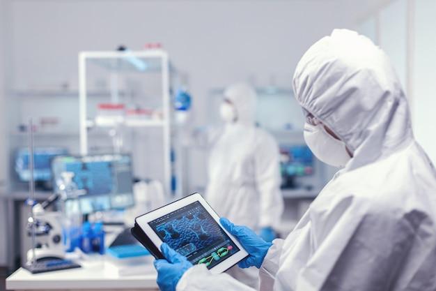 コロナウイルス感染に対する防護服を着たデジタルタブレットを使用する集中医学研究者。解像度のためのハイテク技術を使用してワクチン開発を行う科学者のチーム