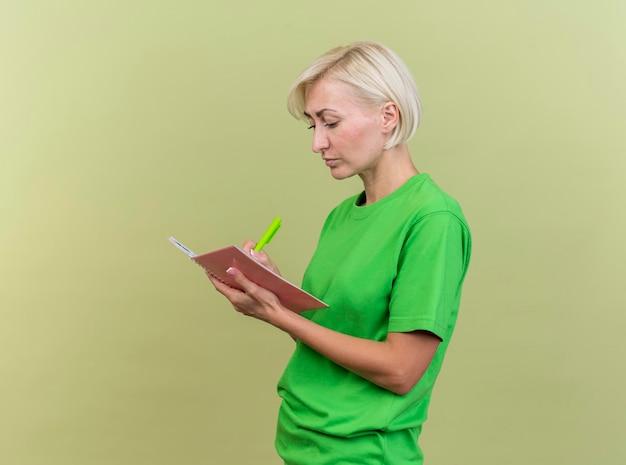 Сосредоточенная белокурая славянская женщина средних лет, стоящая в профиль, пишет в блокноте ручкой, изолированной на оливково-зеленой стене с копией пространства