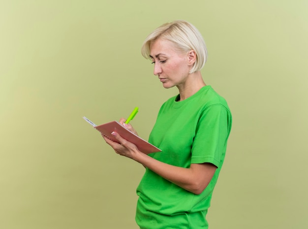 Concentrated middle-aged blonde slavic woman standing in profile view writing on note pad with pen isolated on olive green wall with copy space