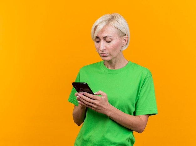 노란색 벽에 고립 된 그녀의 휴대 전화를 사용하여 집중된 중년 금발의 여자